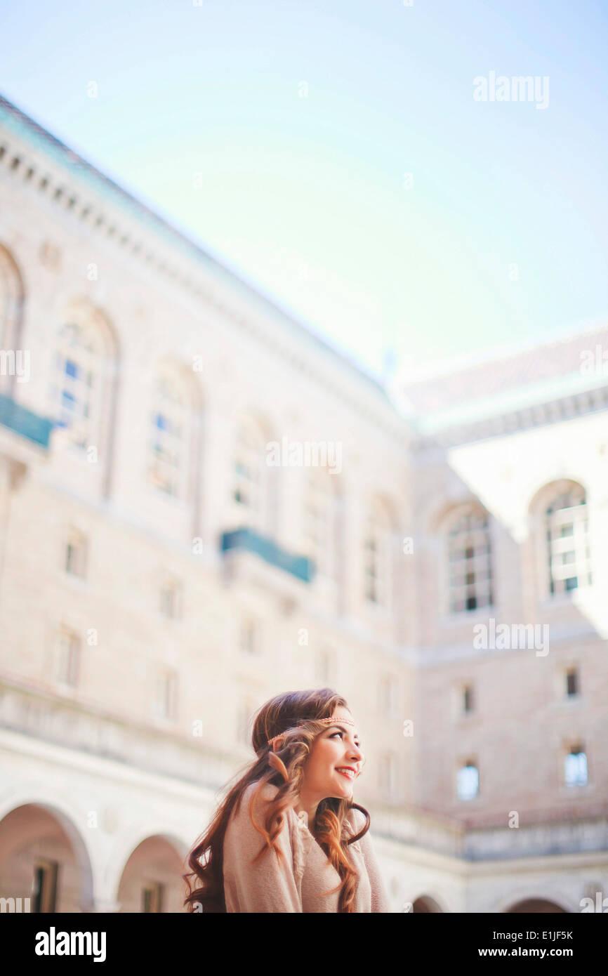 Young woman gazing upward in historic courtyard - Stock Image