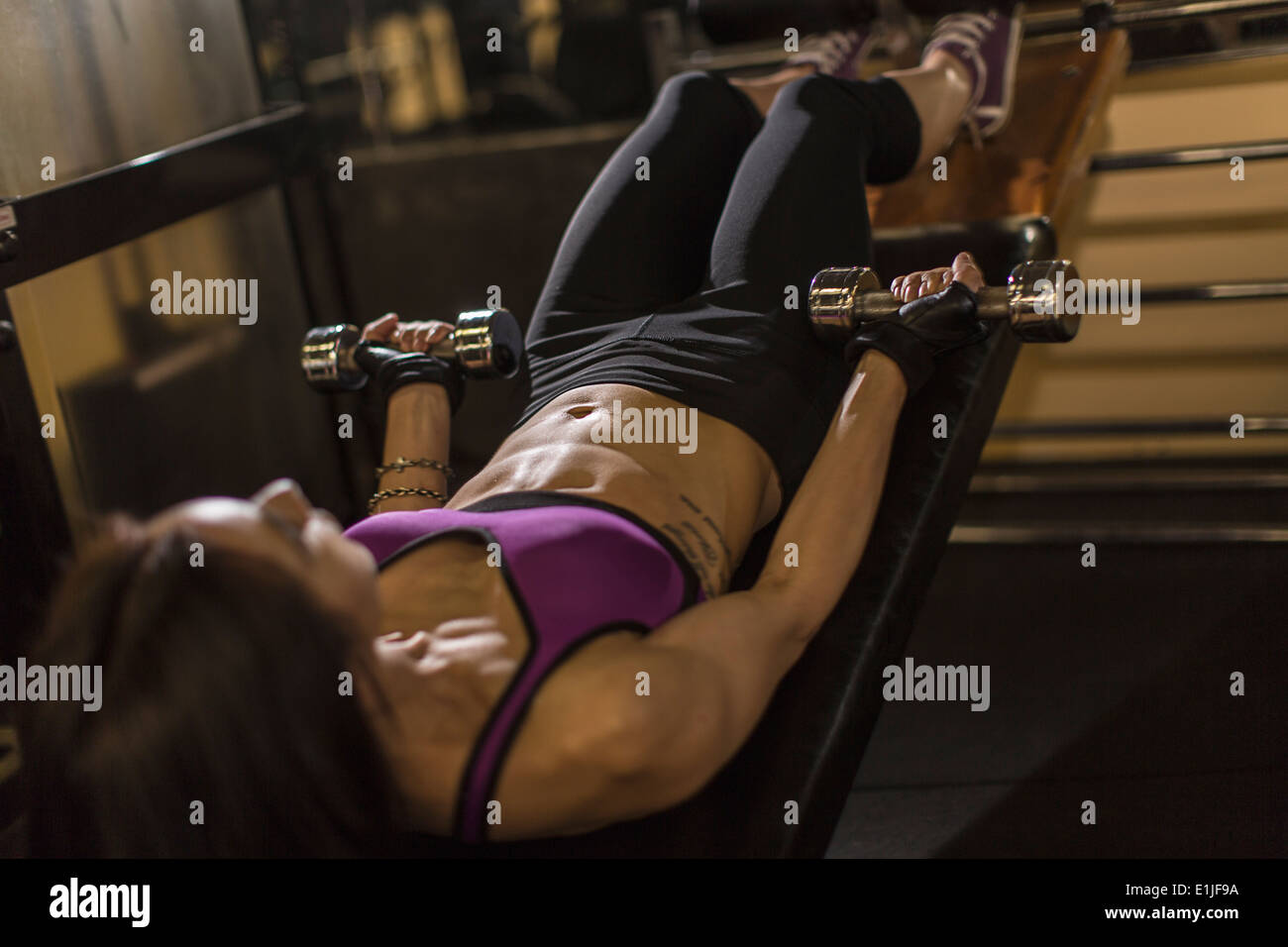 Mid adult woman using dumbbells on weight bench Stock Photo