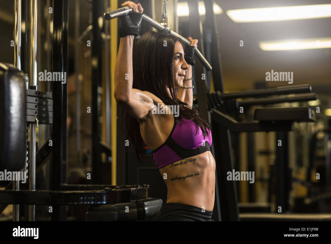 Mid adult woman in gym doing pectoral exercise Stock Photo