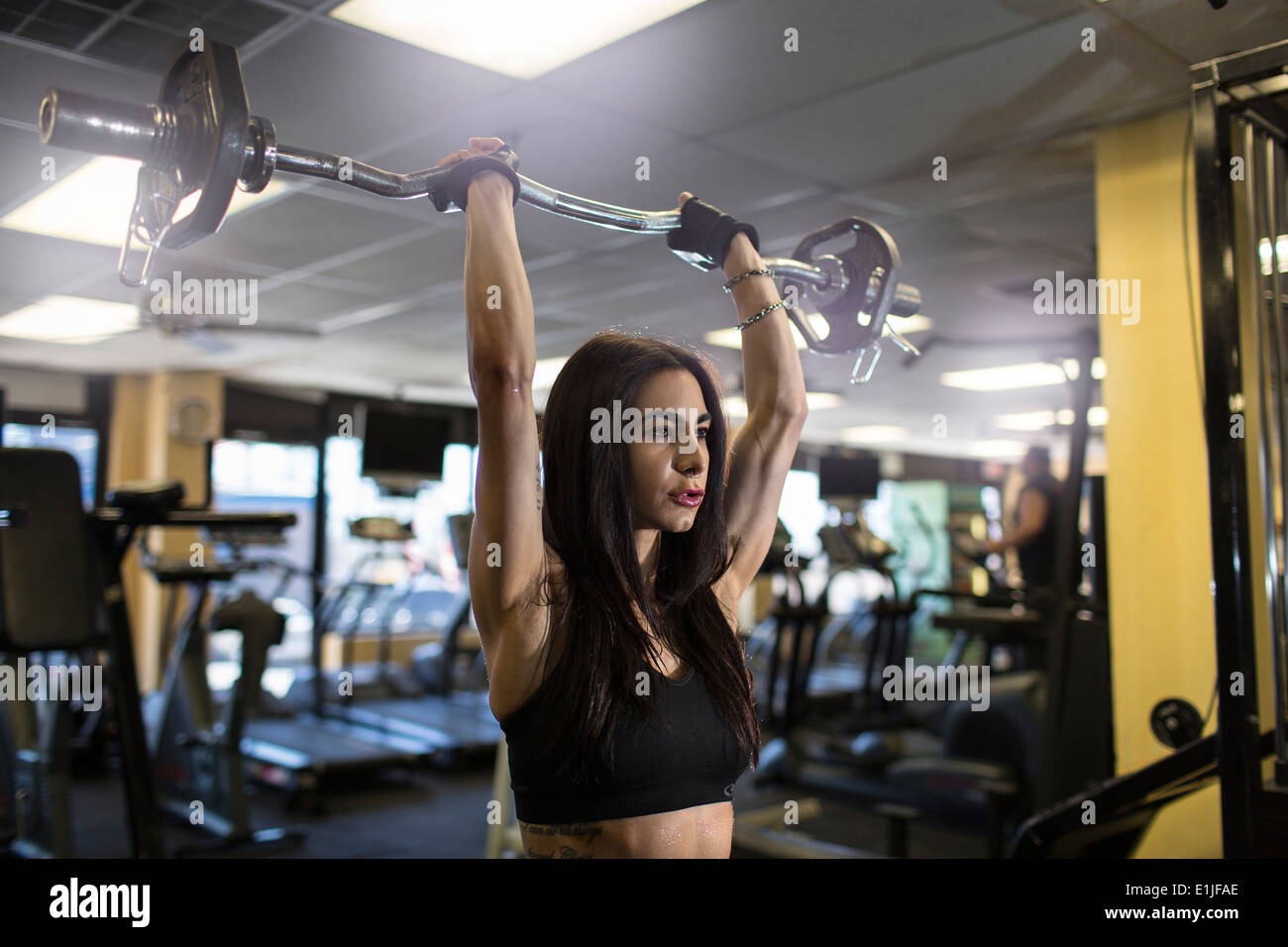 Mid adult woman using barbell in gym - Stock Image