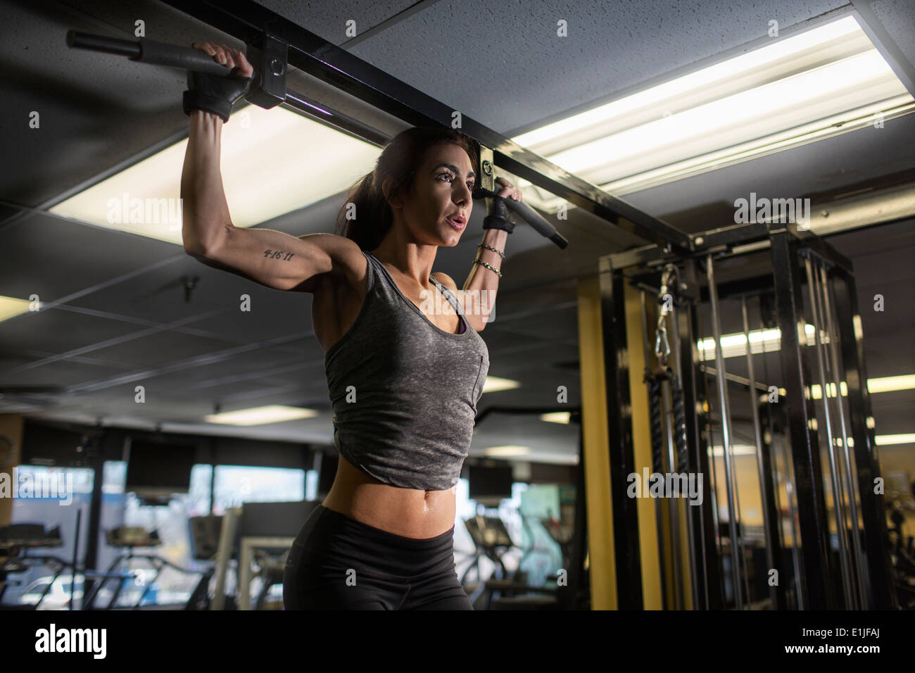 Mid adult woman doing pectoral exercise in gym - Stock Image