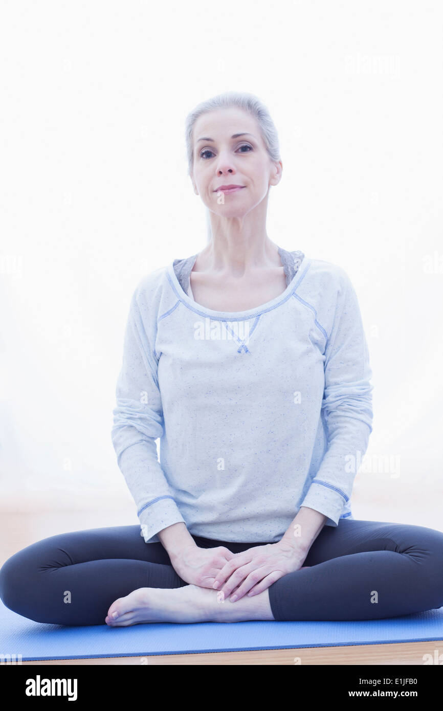 Mature woman in lotus pose - Stock Image