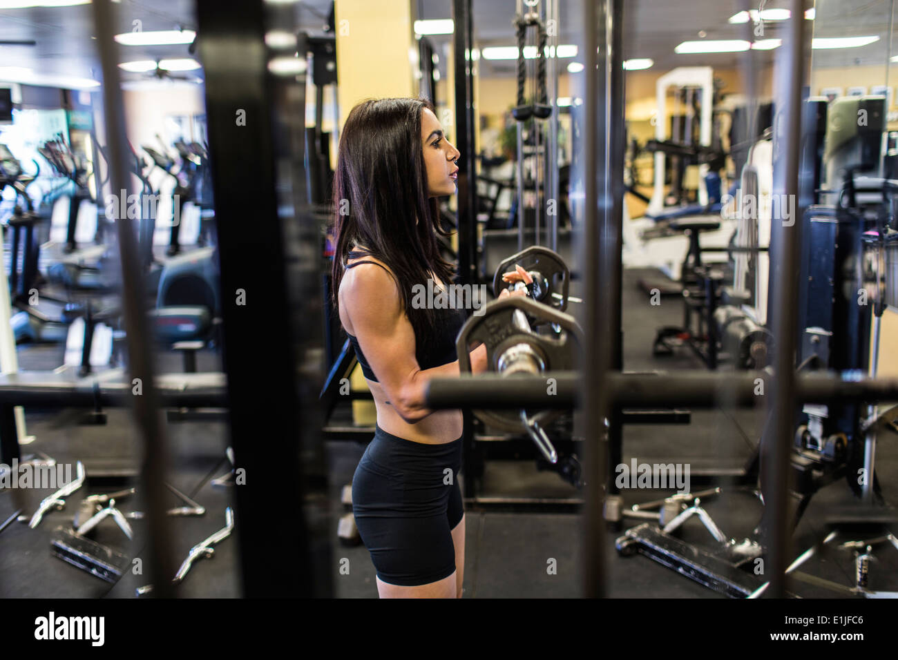 Mid adult woman weightlifting barbell in gym Stock Photo