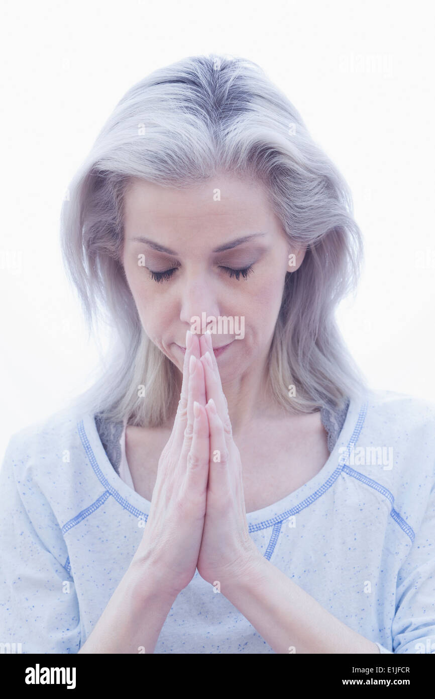 Mature woman in prayer pose - Stock Image