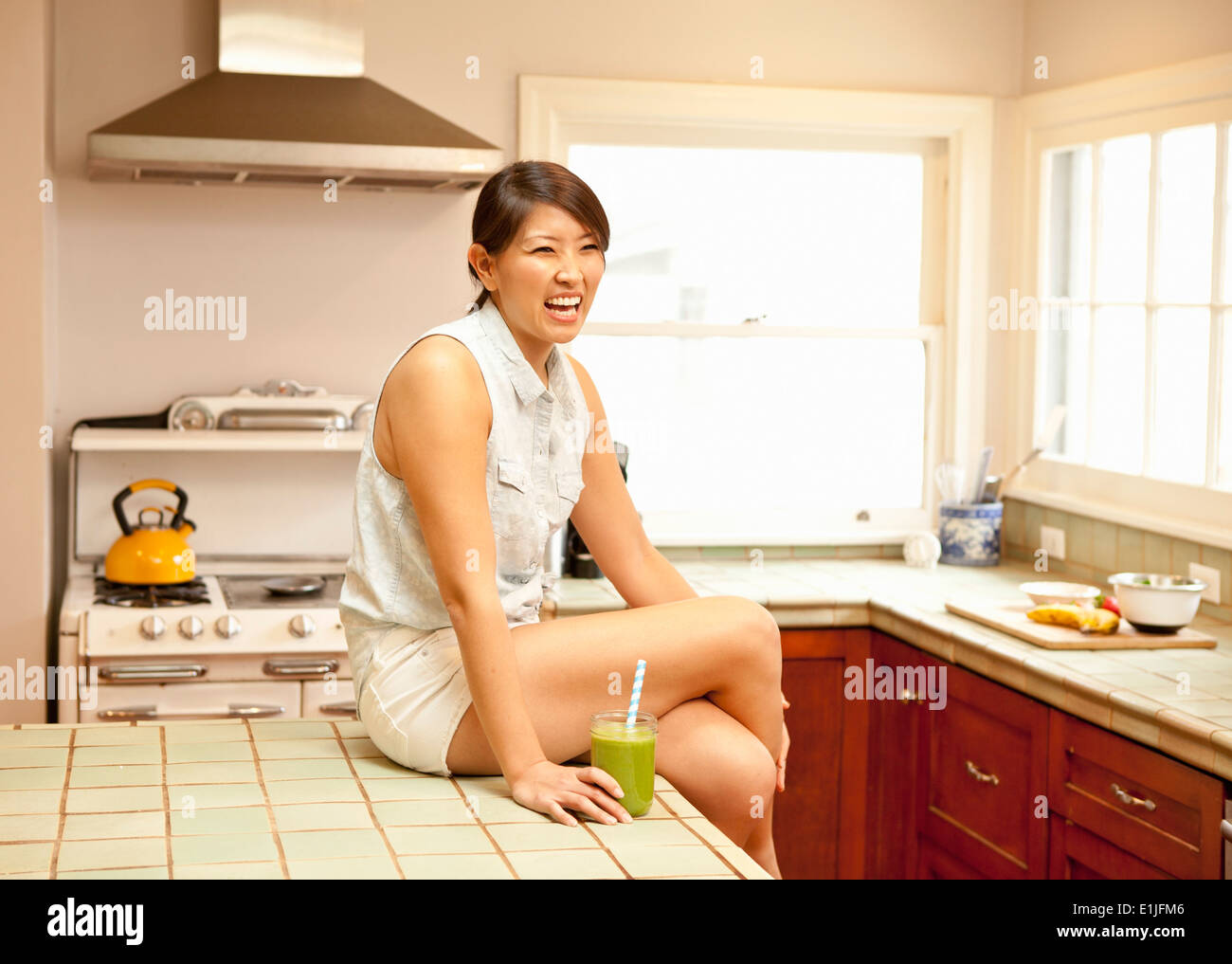 Young woman with green smoothie in kitchen - Stock Image
