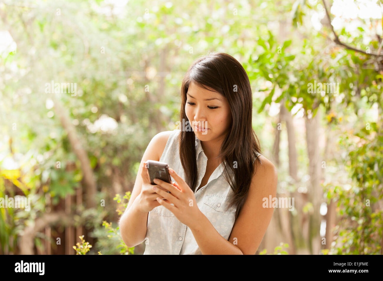 Young woman using smart phone - Stock Image