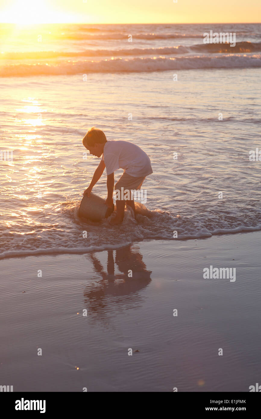 Boy fetching sea water with bucket - Stock Image
