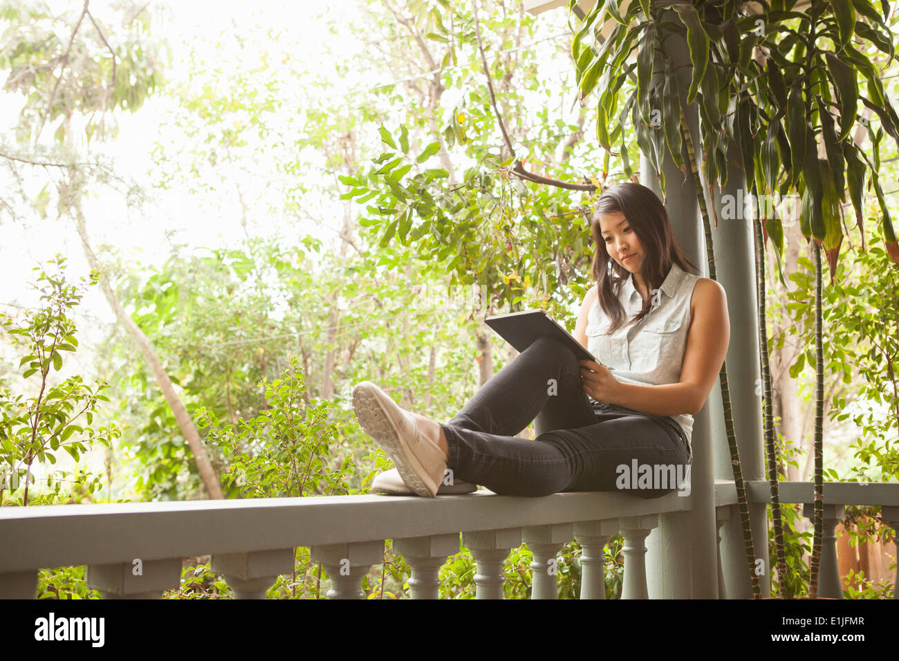 Young woman using digital tablet on porch - Stock Image