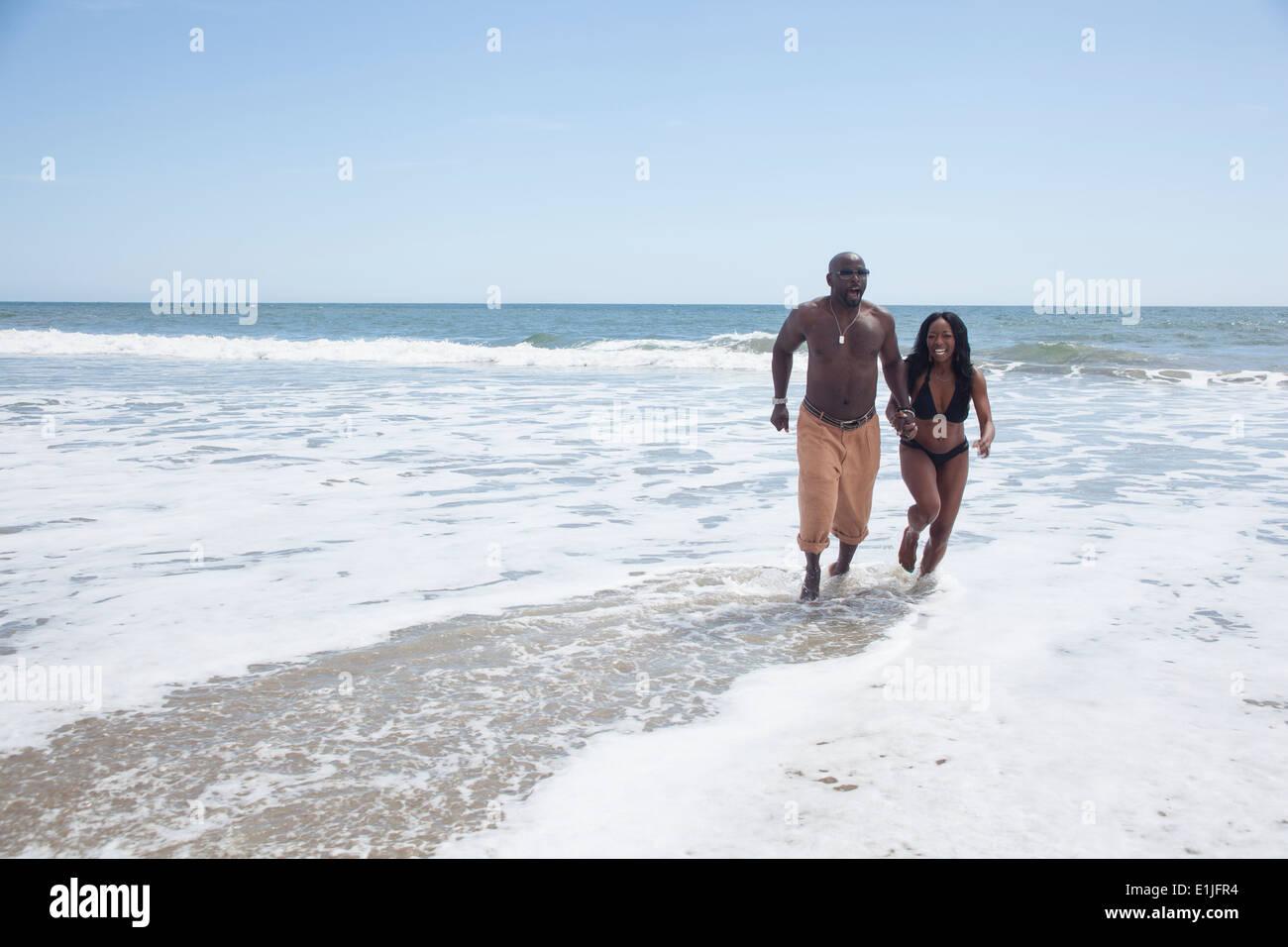 Mature couple walking on beach - Stock Image