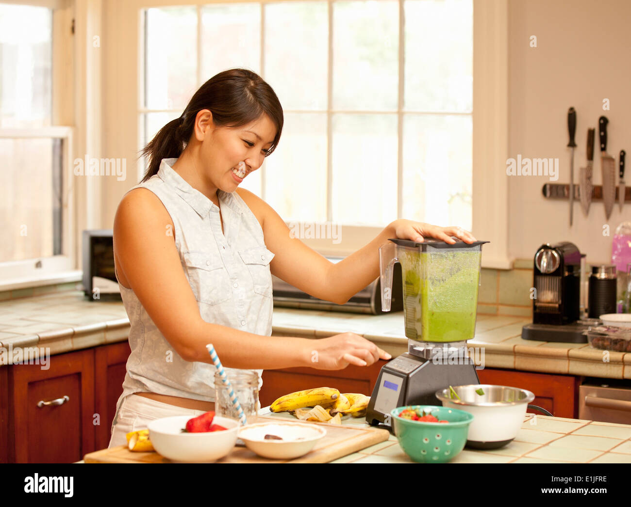 Young woman making green smoothie in kitchen - Stock Image