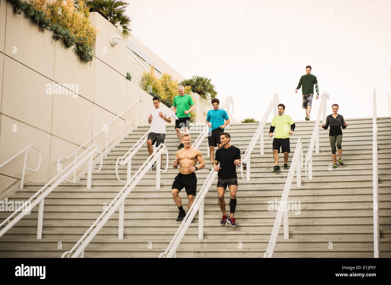 Small group of runners training on convention center stairs - Stock Image