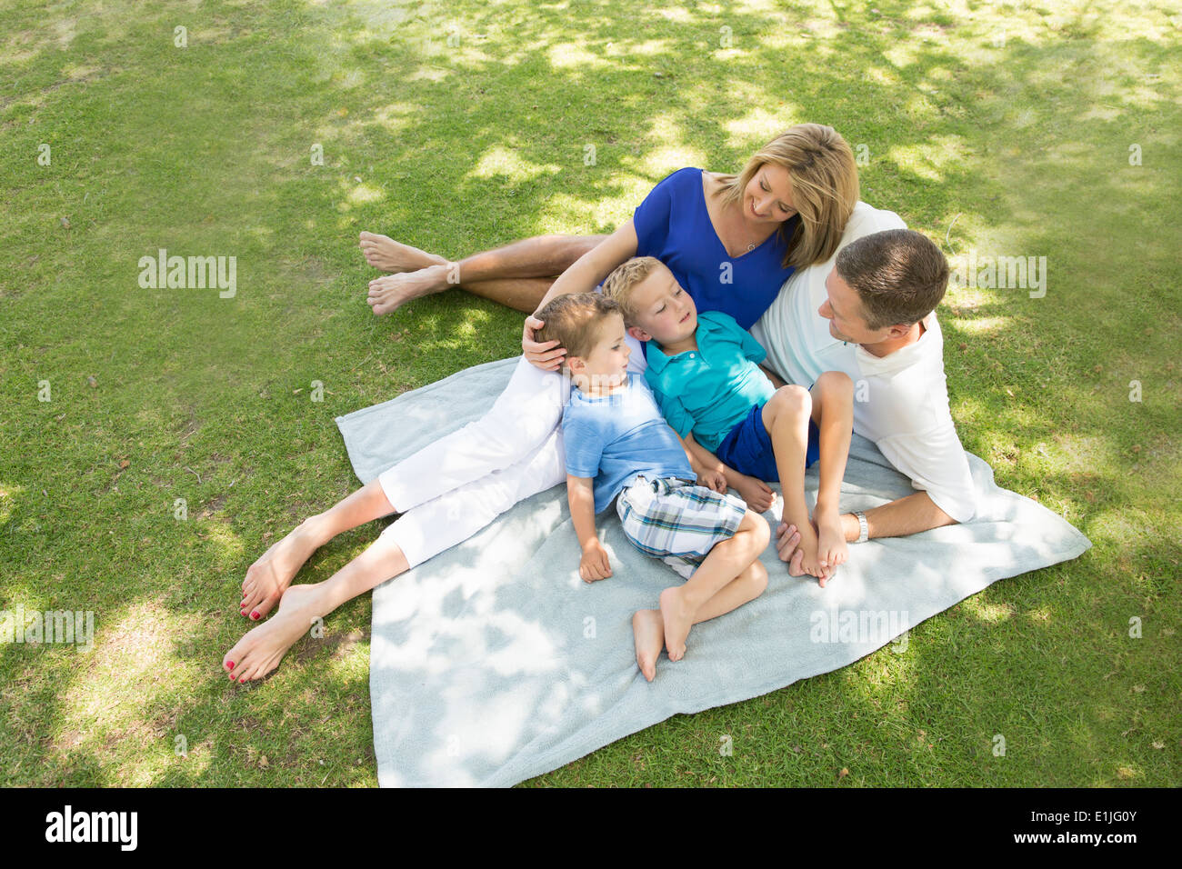 Family of four on picnic blanket - Stock Image