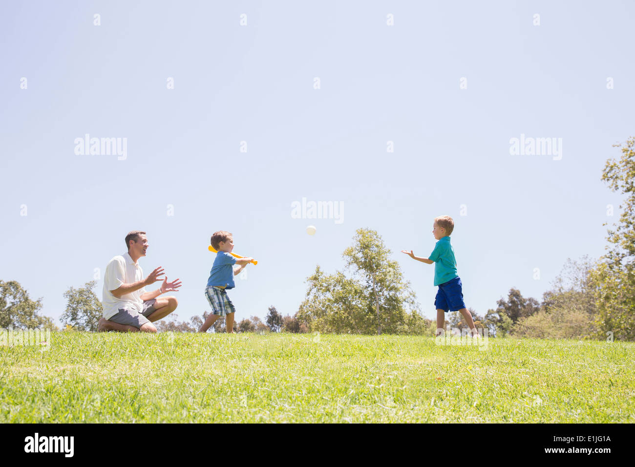 Father and sons playing baseball at park - Stock Image