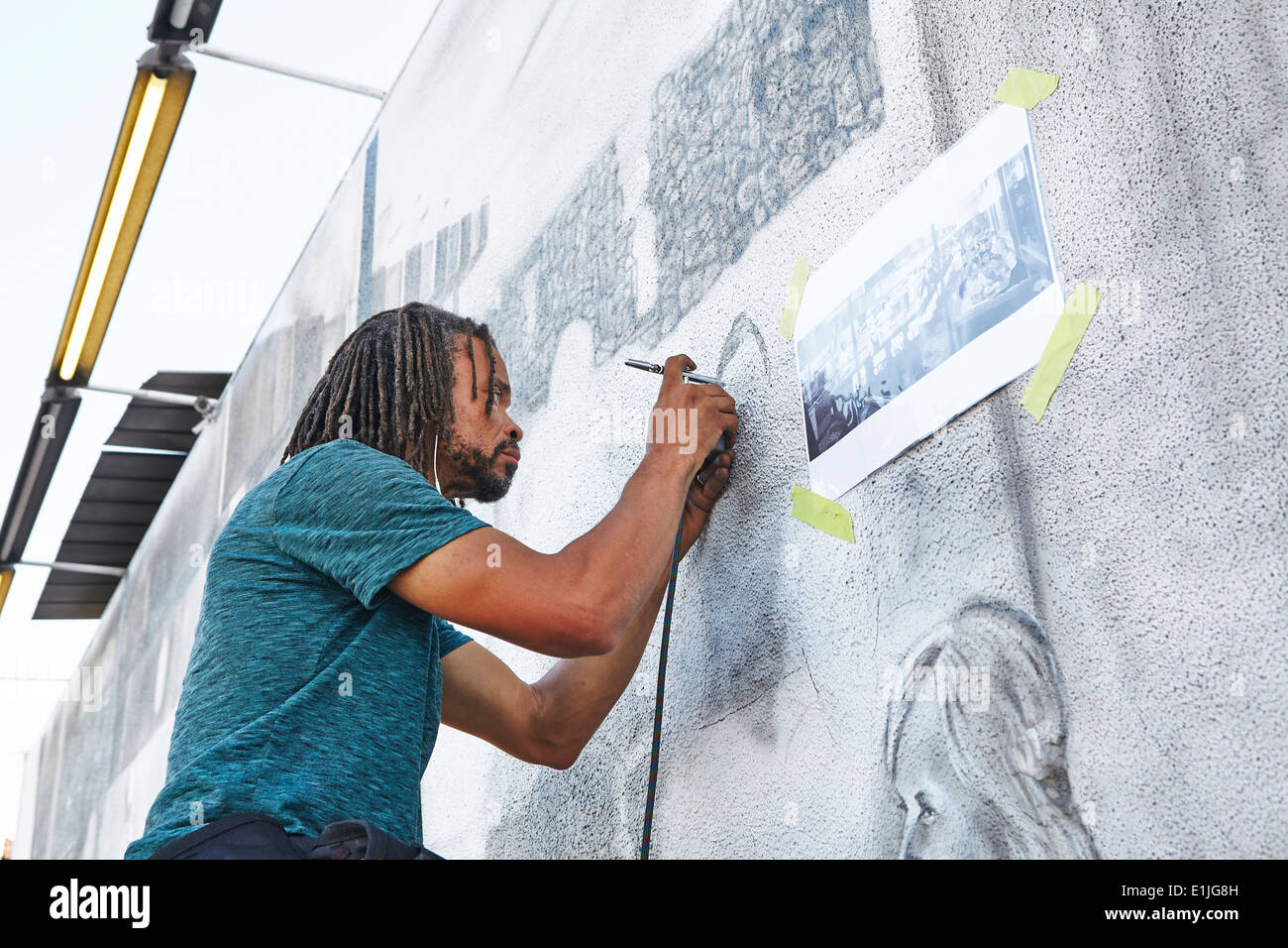 Male african american airbrush artist painting mural - Stock Image