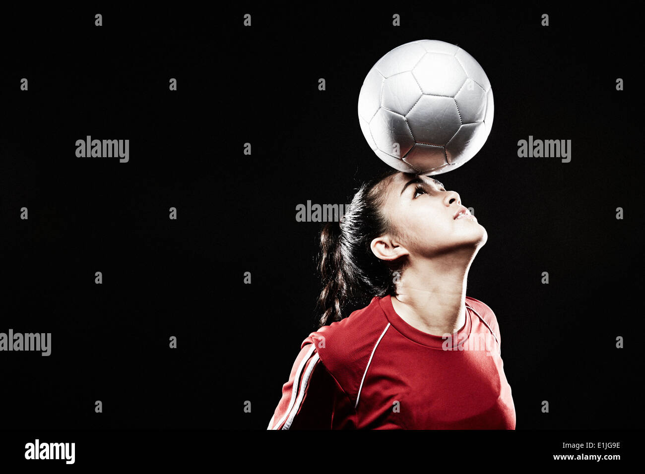 Young woman balancing football on forehead - Stock Image