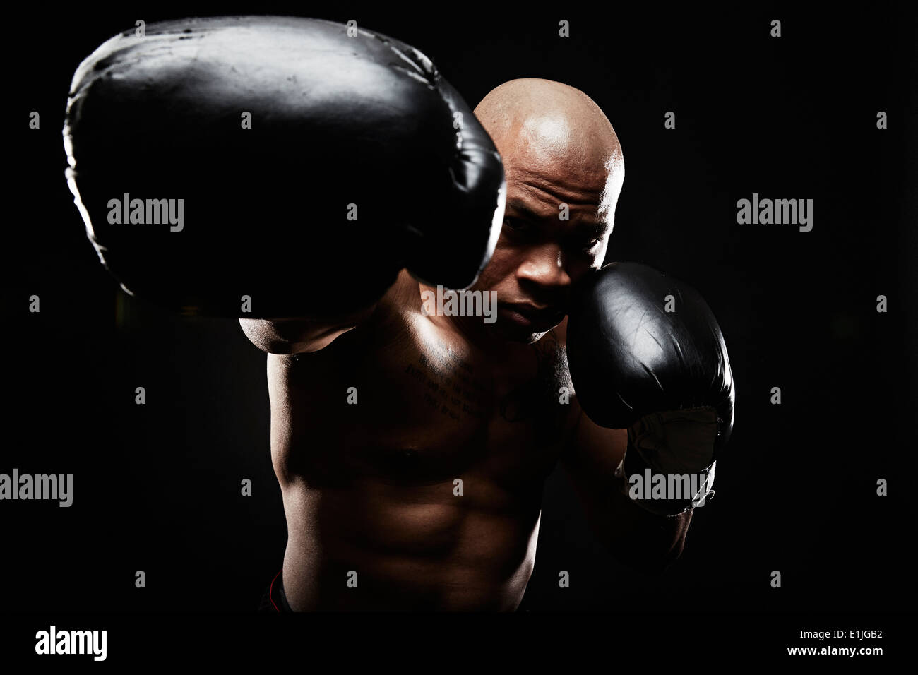 Boxer with black boxing gloves punching towards camera - Stock Image