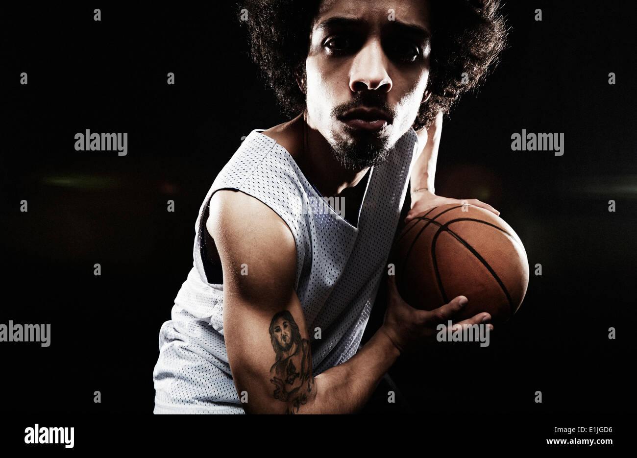 Basketball player holding basketball - Stock Image