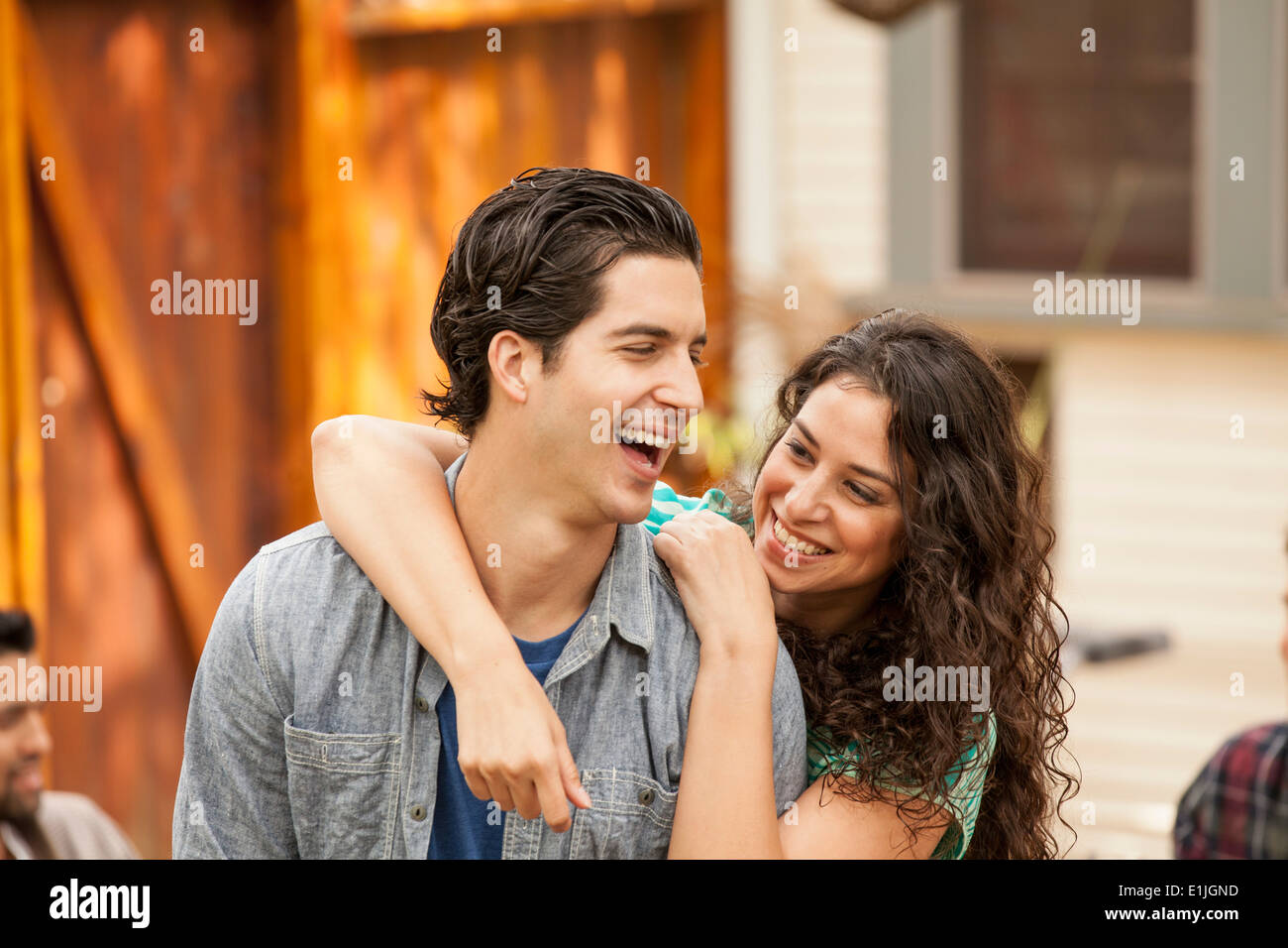 Couple in garden, with arm around, friends in background - Stock Image