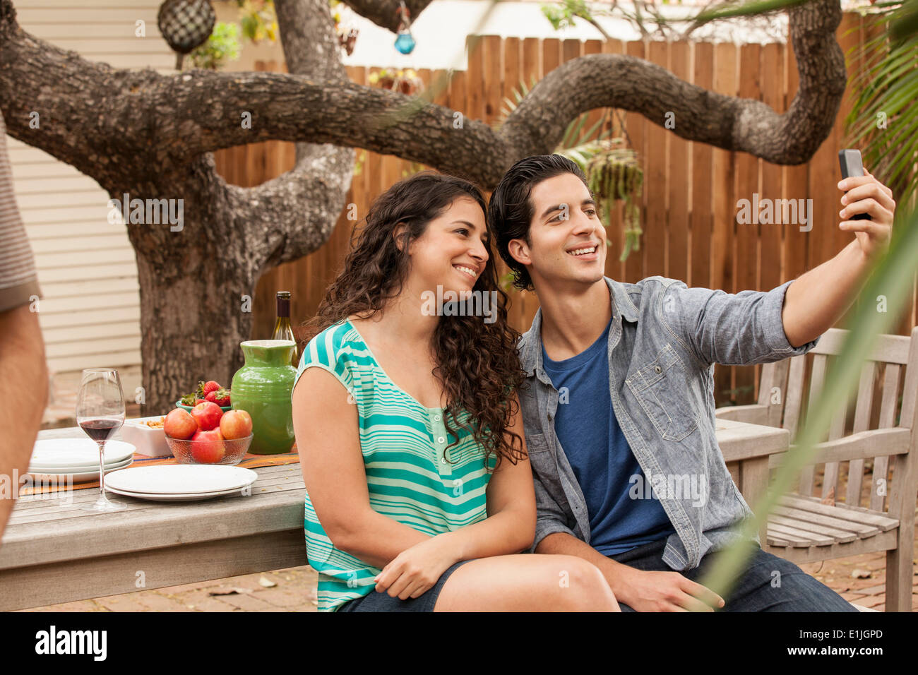 Couple taking self portrait photograph using smartphone - Stock Image
