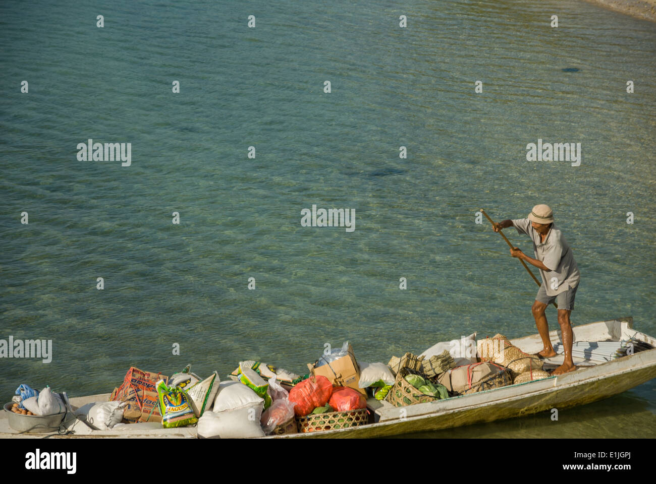 Food trasport by boat with a man Nusa Lembongan Indonesia Stock Photo