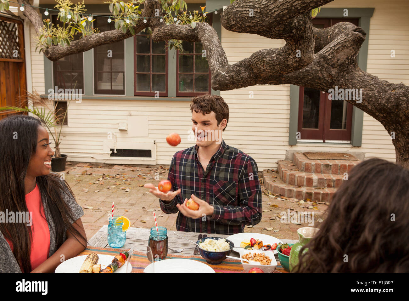 Friends sitting around table sharing barbecue food, man juggling fruit - Stock Image