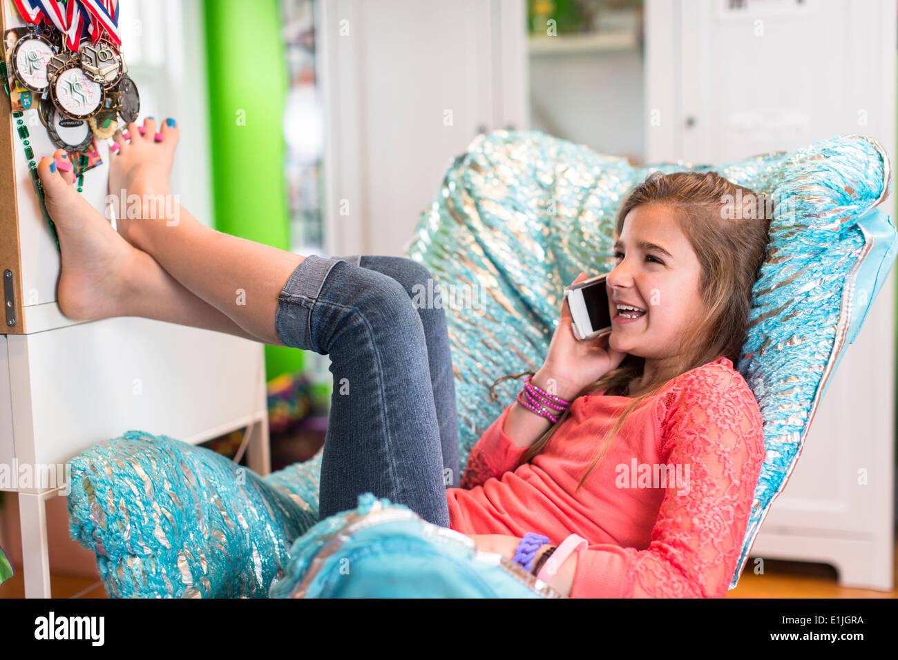 Girl sitting on armchair on phonecall - Stock Image