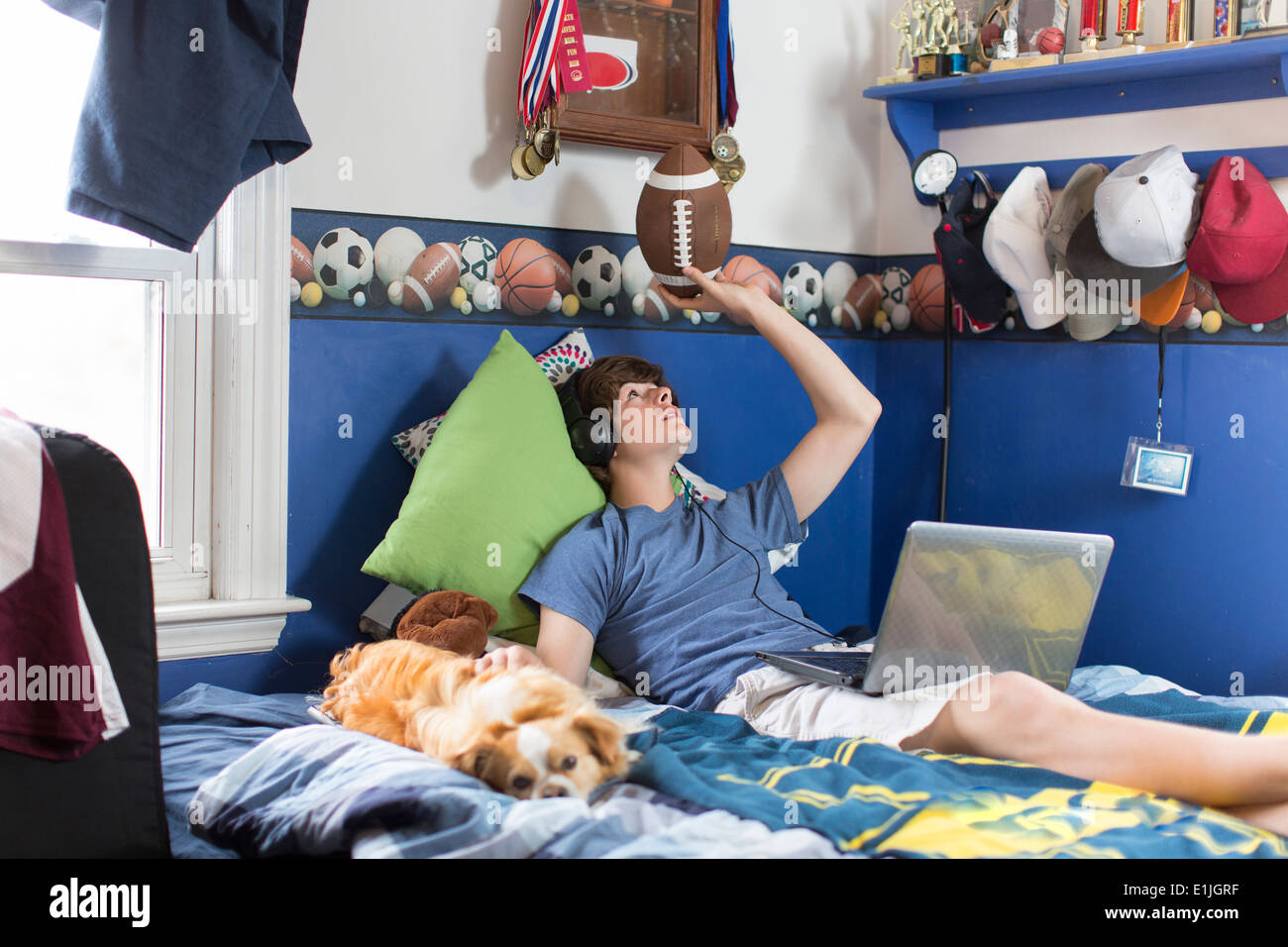 Teenage boy lying on bed with laptop computer, football and dog Stock Photo