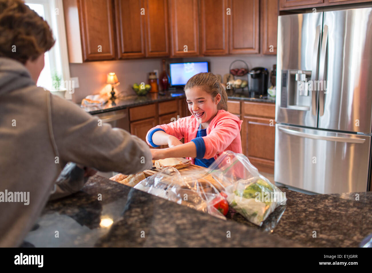 Brother and sister in kitchen preparing sandwich - Stock Image
