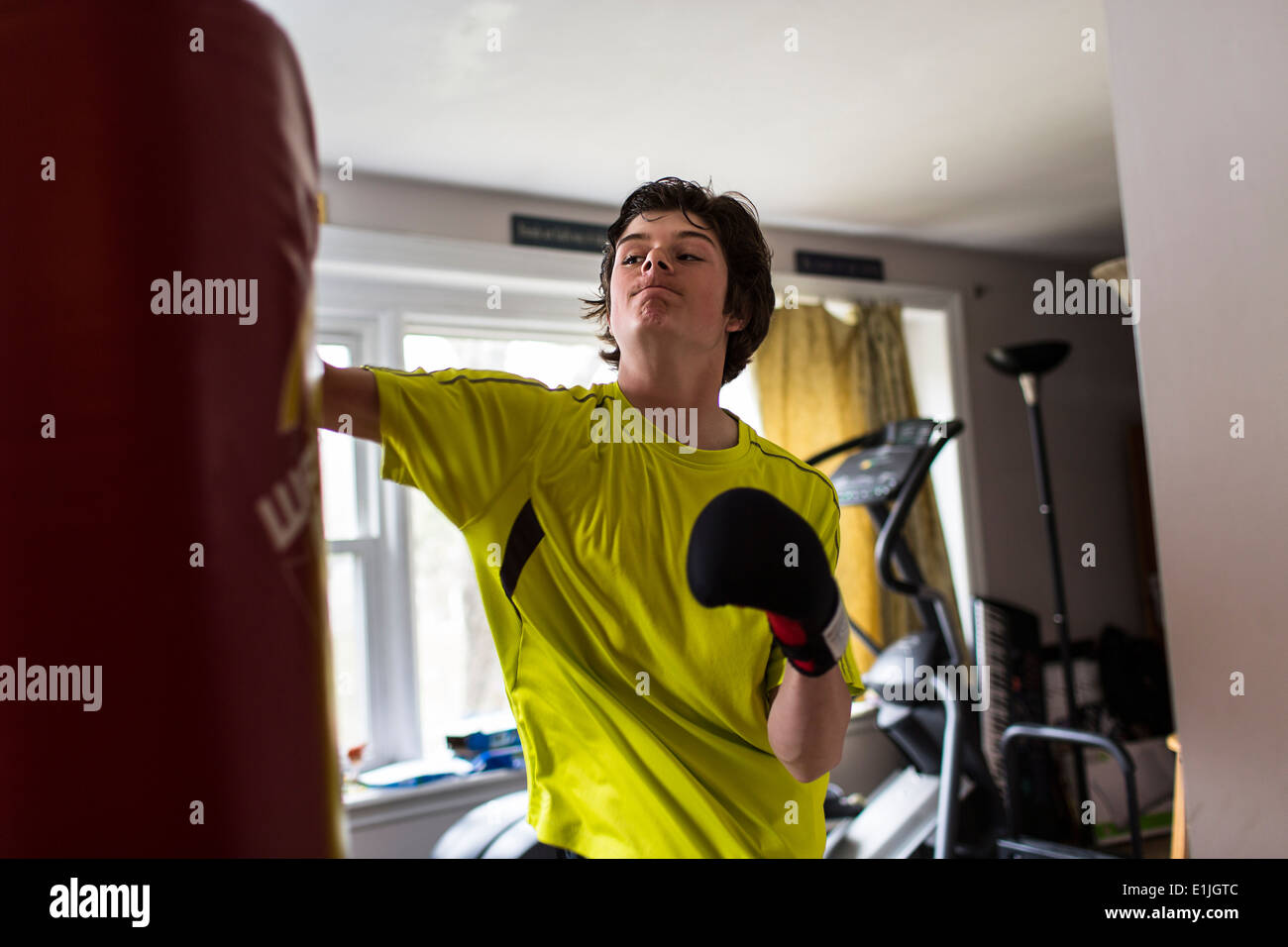 Teenage boy wearing boxing gloves Stock Photo