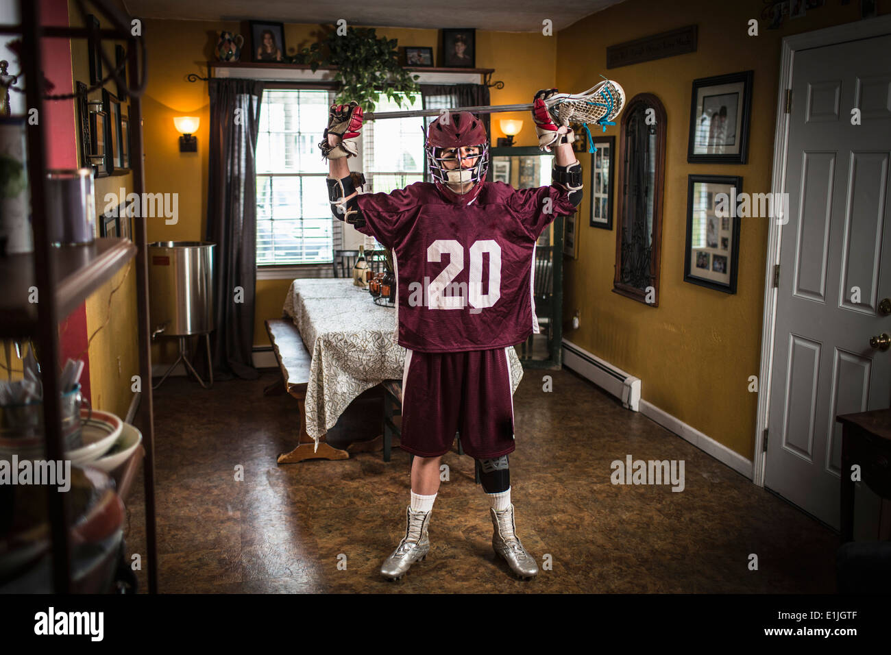 Teenage boy wearing lacrosse uniform, standing in dining room Stock Photo