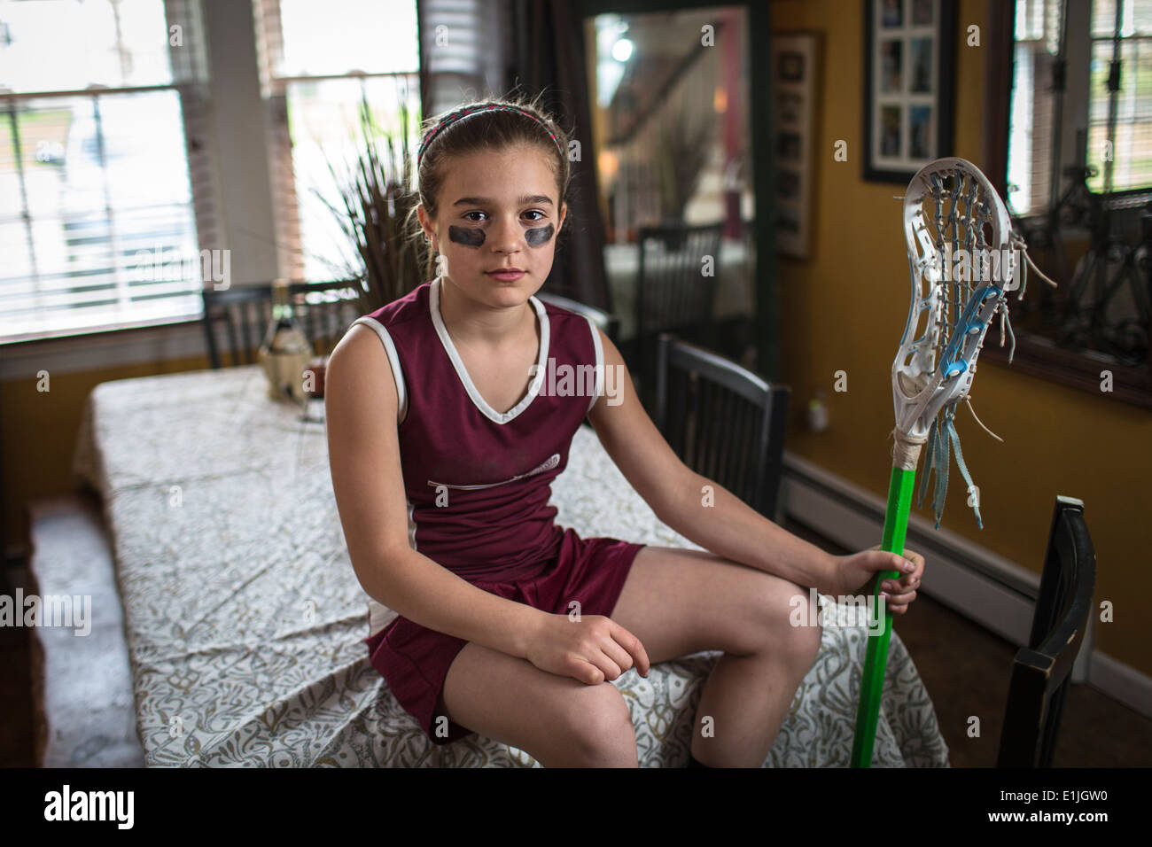 Girl wearing lacrosse uniform, sitting on dining table - Stock Image