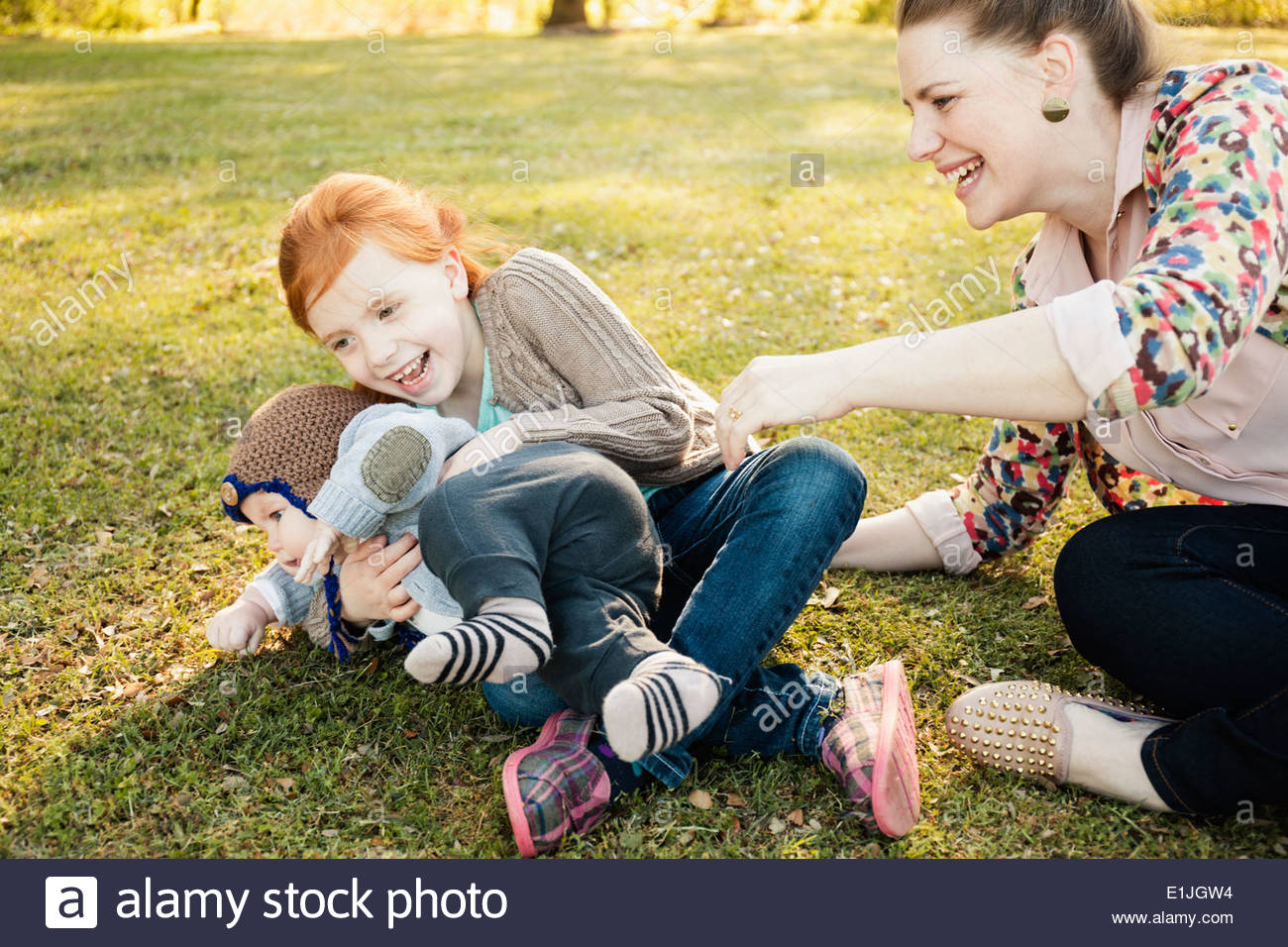 Mid adult mother, daughter and baby son on grass in park - Stock Image