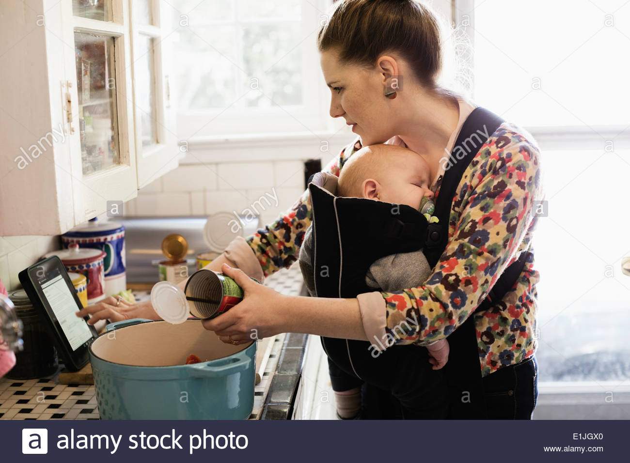 Mid adult mother with baby son in sling preparing food in kitchen - Stock Image