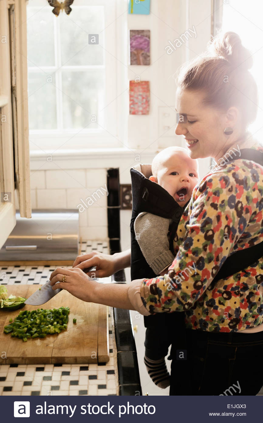 Mid adult mother preparing food with baby son in sling Stock Photo