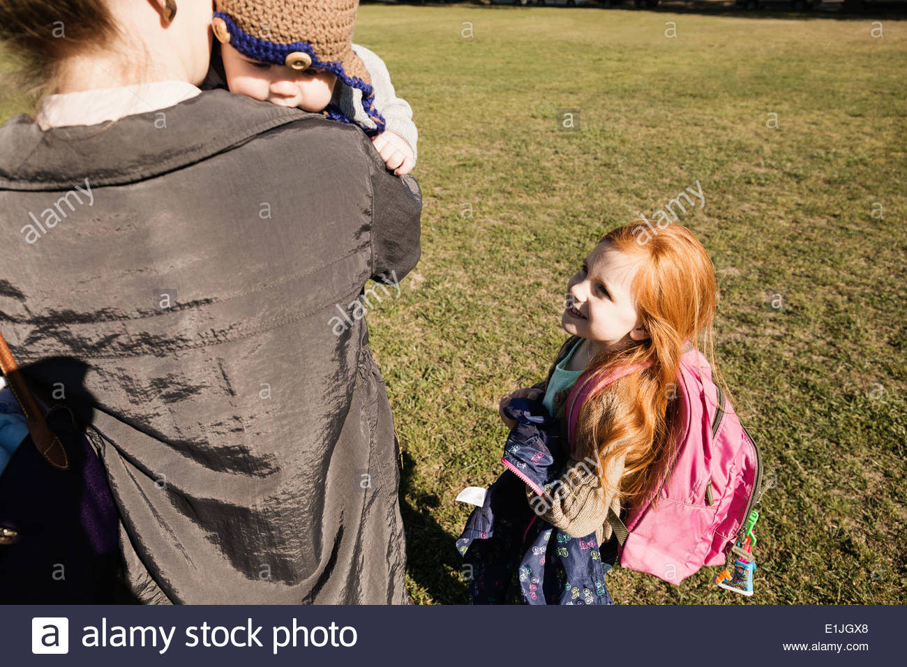 Mid adult mother, baby son and daughter strolling in park - Stock Image