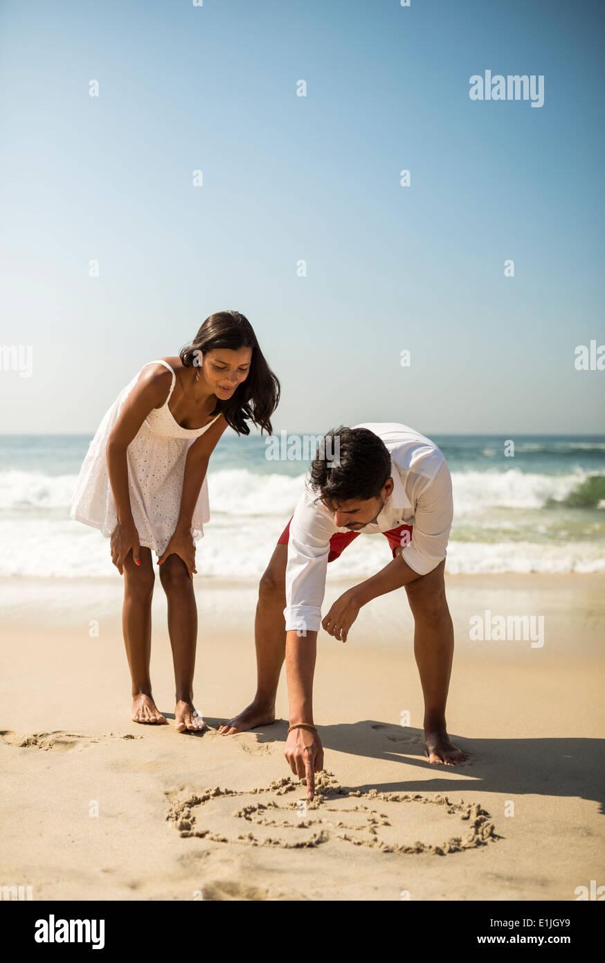 Couple drawing in sand on Arpoador beach, Rio De Janeiro, Brazil - Stock Image
