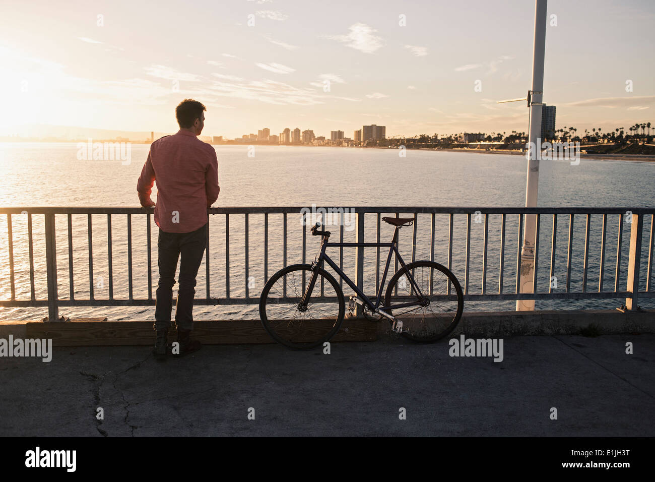 Young man gazing from pier, Long Beach, California, USA - Stock Image