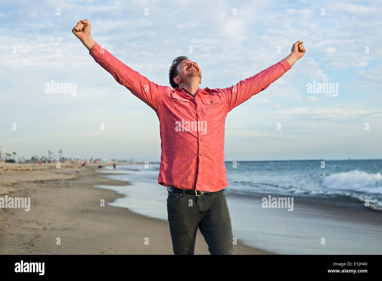 Young man celebrating on beach, Long Beach, California, USA - Stock Image