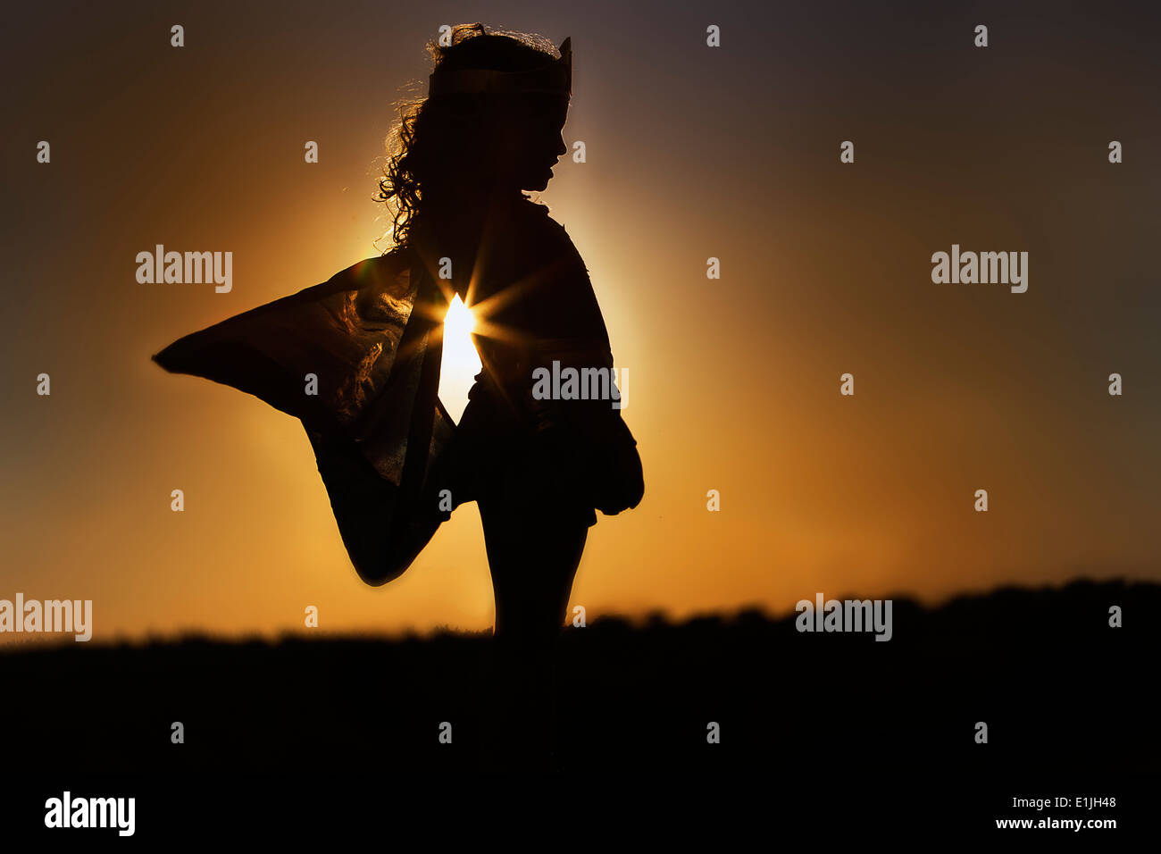 Silhouette of young girl in winged fairy costume at sunset - Stock Image
