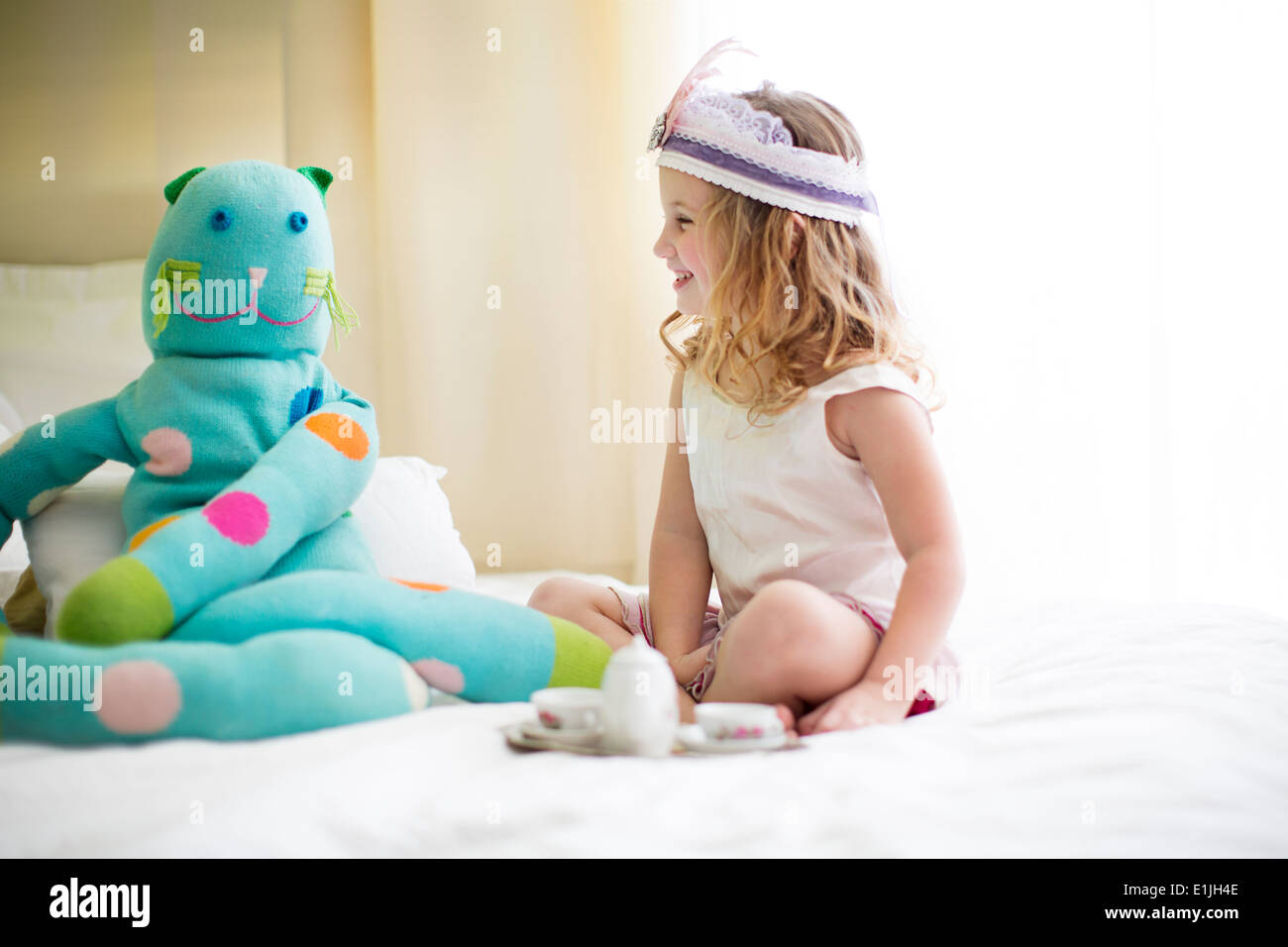 Young girl sharing tea with cuddly toy on bed - Stock Image