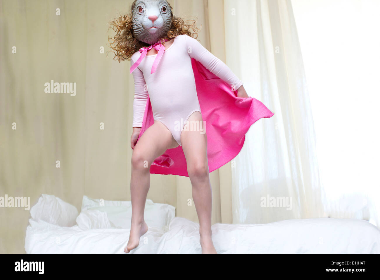 Young girl dressed up as a rabbit princess dancing on bed - Stock Image