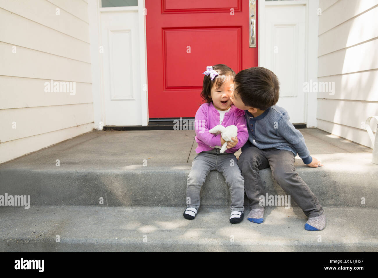 Brother kissing toddler sister on cheek Stock Photo