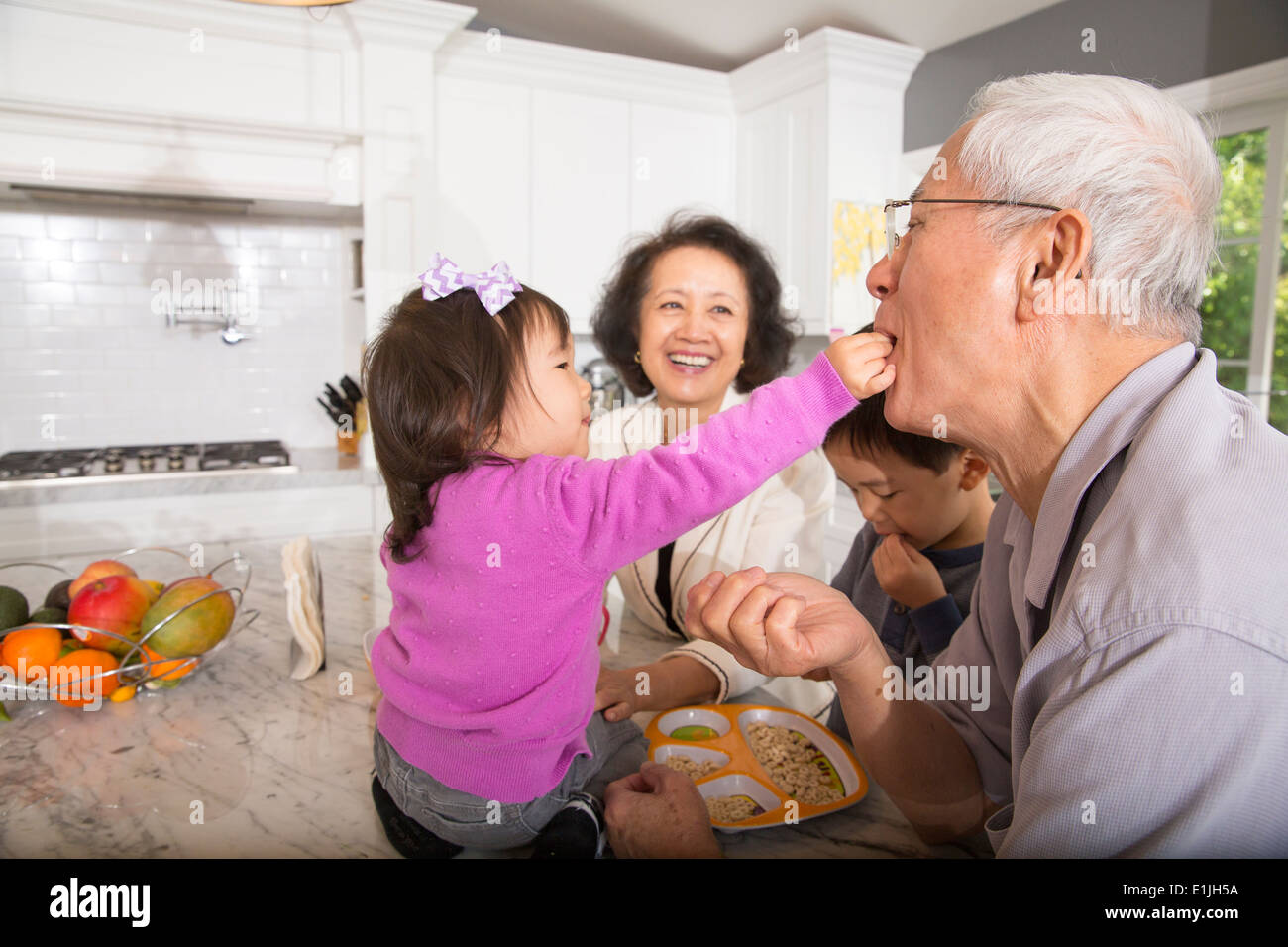 Female toddler feeding snack to grandfather in kitchen - Stock Image