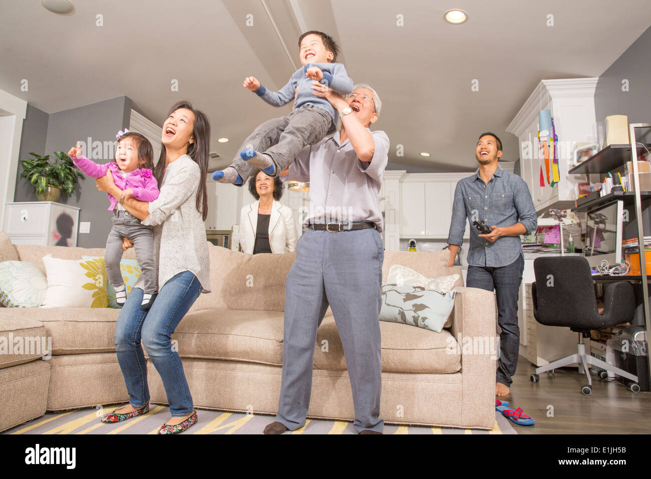 Three generation family having fun in sitting room - Stock Image