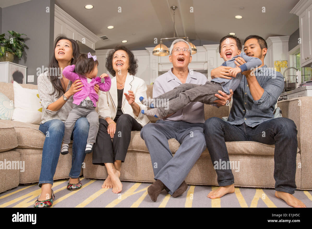Three generation family playing together on sofa - Stock Image