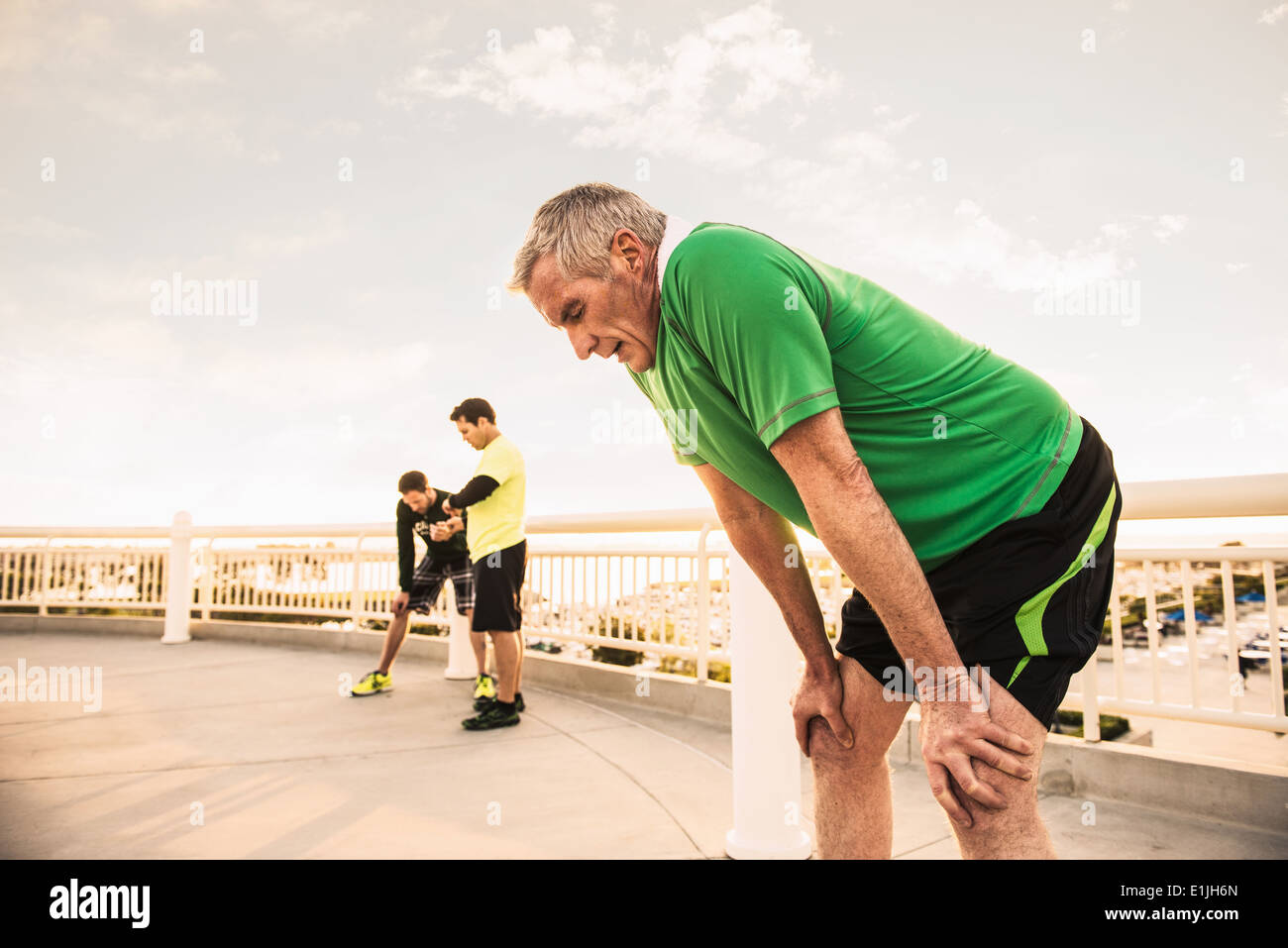 Exhausted male runners taking a break from training - Stock Image
