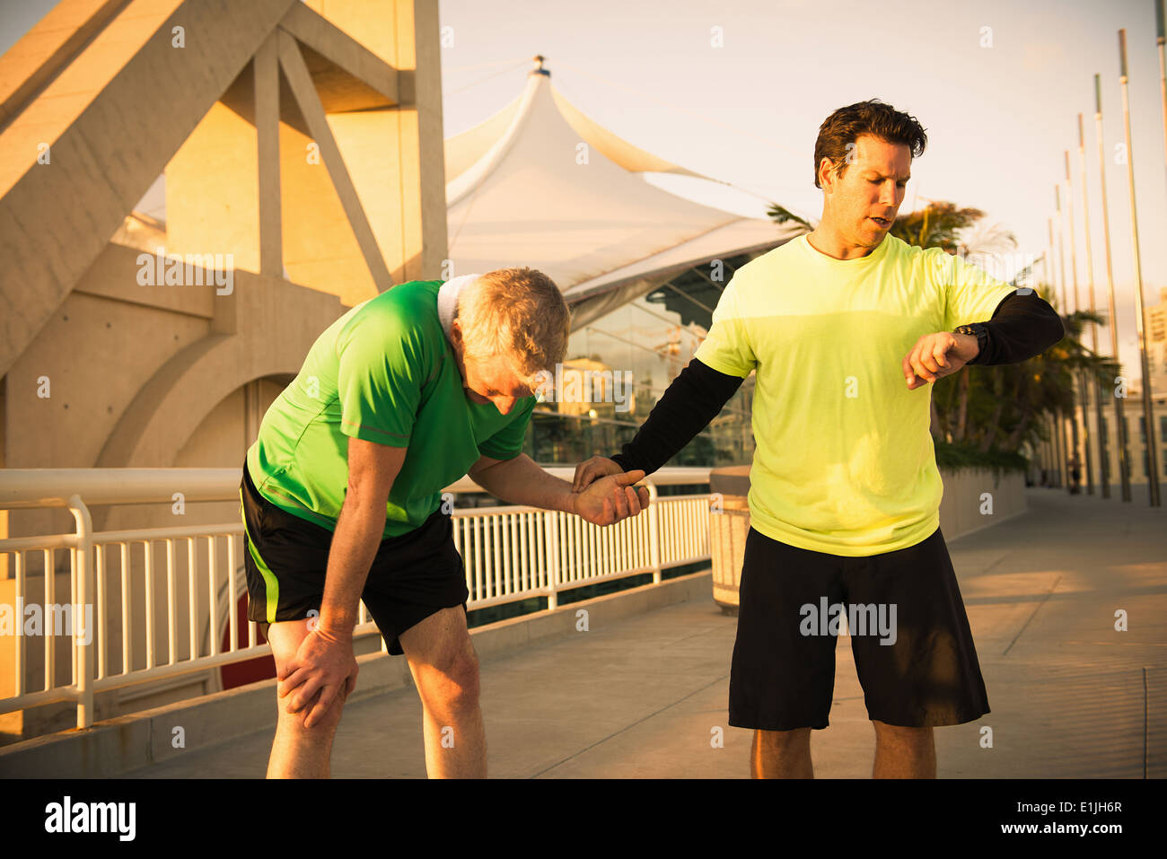 Exhausted male runner with trainer checking pulse - Stock Image