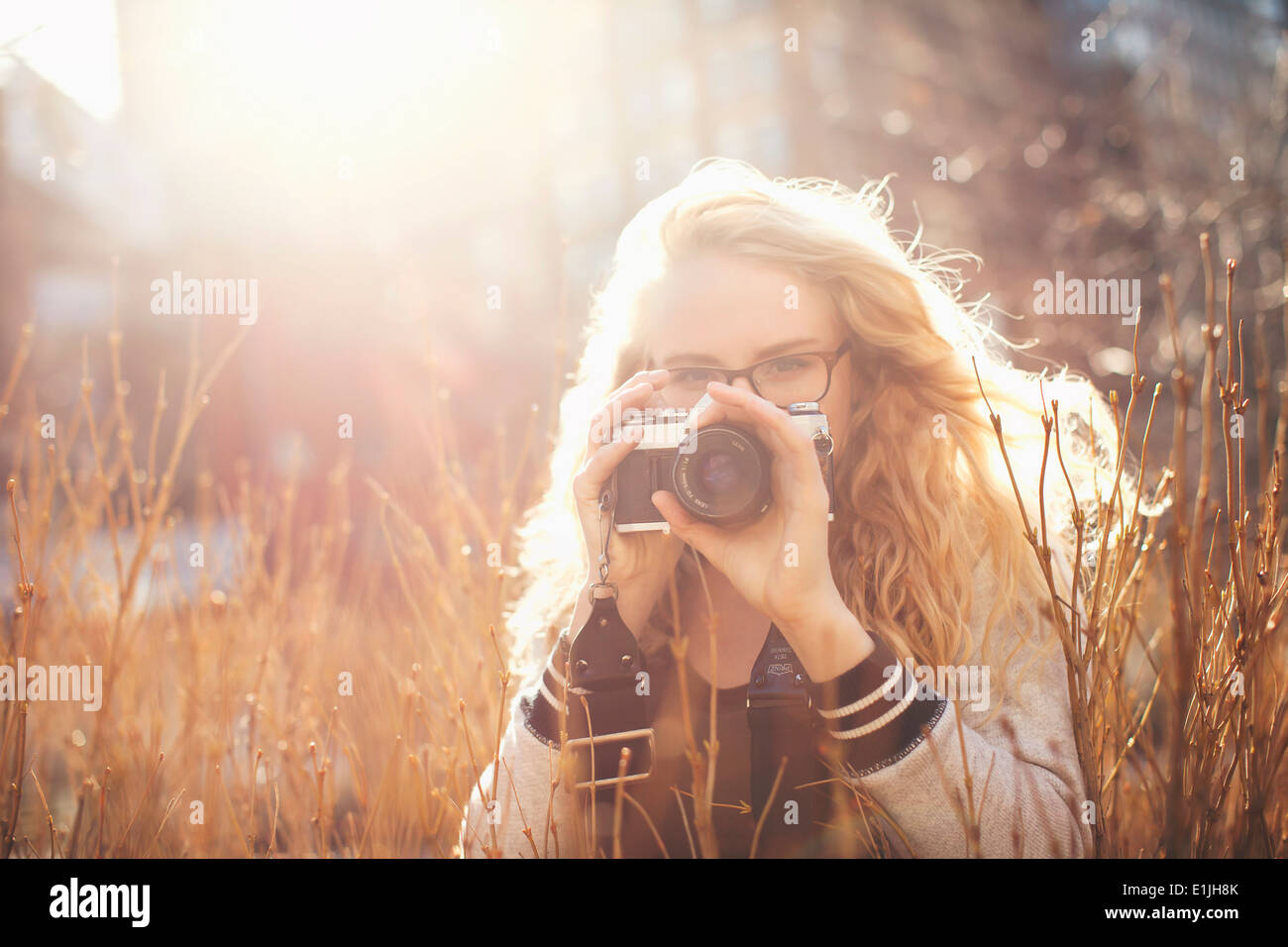 Young woman taking photograph - Stock Image