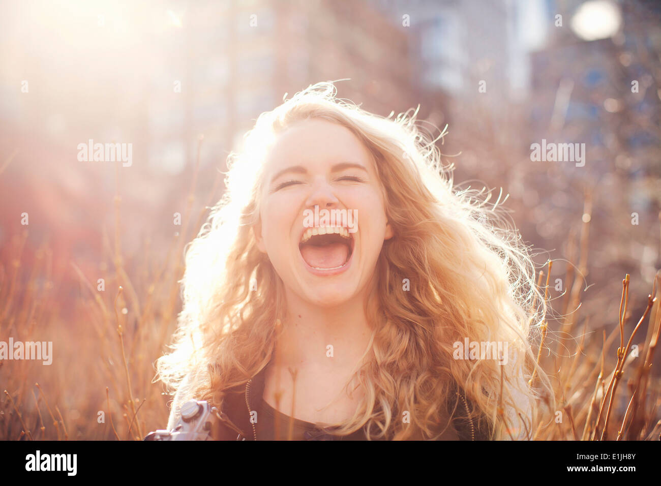 Young woman in long grass with open mouth - Stock Image