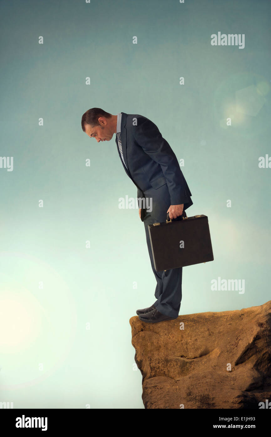 businessman on the edge of a cliff or brink of a crevasse looking down - Stock Image